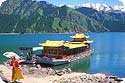 Uygur lady and tourist boat in ��� Tianchi